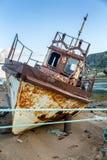 Un bateau rouillé abandonné sur une plage sablonneuse photo stock