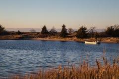 Un bateau solitaire au coucher du soleil, port de fléchissement, New York photographie stock