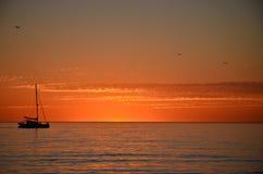 Un bateau sur l'horizon au coucher du soleil Photos stock