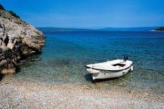 Un bateau sur une plage rocheuse avec des montagnes dans le dos Image libre de droits