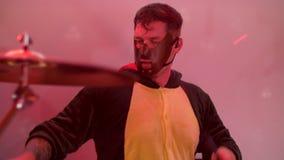 Un batería en una máscara juega los tambores en un concierto almacen de video
