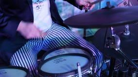 Un batterista irriconoscibile in un rivestimento, un uomo che gioca i tamburi, un batterista in una banda di musica, uno spettaco video d archivio