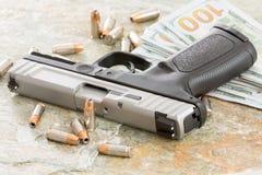 Un batuffolo di 100 banconote in dollari con una pistola e le pallottole Immagini Stock