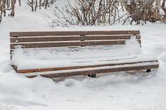 Un beau banc peint en bois de couleur brune avec les supports en fer forgé noirs de jambes avec la neige blanche en parc en hiver photos stock