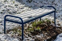 Un beau banc peint en bois humide lumineux de couleur bleue avec les jambes bleues en métal avec les supports blancs de neige sur photographie stock libre de droits