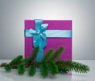 Un beau boîte-cadeau dans le bleu, avec un ruban et un arc pourpres Avant elle est une branche d'un arbre de Noël Beau Photographie stock libre de droits