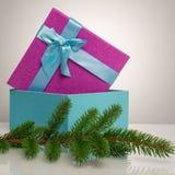 Un beau boîte-cadeau dans le bleu, avec un ruban et un arc pourpres Avant elle est une branche verte d'un arbre de Noël Beau Photos libres de droits