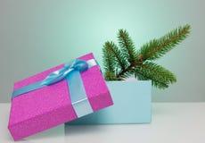 Un beau boîte-cadeau dans le bleu, avec un ruban et un arc pourpres Dans elle se trouve une branche d'un arbre de Noël Beau Noël Photographie stock