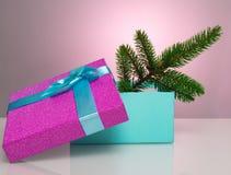 Un beau boîte-cadeau dans le bleu, avec un ruban et un arc pourpres Dans elle se trouve une branche d'un arbre de Noël Beau Noël Image stock