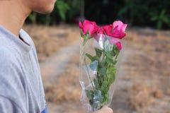 Un beau bouquet des roses rouges est tenu en main du jeune homme décontracté sur le fond extérieur de nature ` S de Valentine d'h Image stock