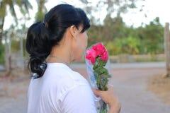 Un beau bouquet des roses rouges sont tenus par la femme âgée par milieu asiatique sur le fond brouillé par nature ` S d de Valen Images libres de droits