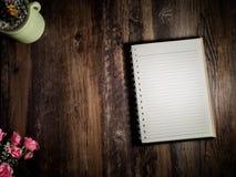 Un beau carnet est placé sur le bureau le bois de brun que foncé avec un rose s'est levé dans en bas à gauche le faisant le coin  Photos stock