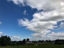 Un beau ciel bleu avec les nuages pelucheux blancs contre le contexte des bâtiments de village et de l'herbe verte Le fond photos libres de droits
