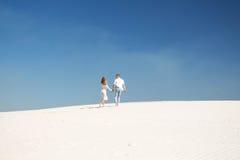 Un beau couple dans la distance parmi les sables illimités blancs Photo libre de droits