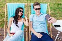 Un beau couple dans les lunettes de soleil se trouve sur les chaises de plate-forme sur la pelouse dans le café bon d'été diverti photos stock
