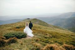 Un beau couple des jeunes mariées marchant dehors Photos stock