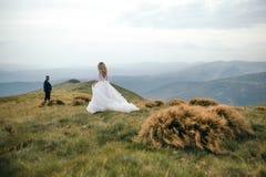 Un beau couple des jeunes mariées marchant dehors Image stock