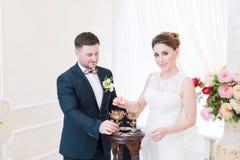 Un beau couple heureux dans le bureau d'enregistrement effectue un rituel de mariage avec l'éclairage de bougie images libres de droits