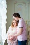 Un beau couple, une jeune femme enceinte et un homme se tiennent près d'une fenêtre, font un coeur à partir des mains sur l'estom Photographie stock