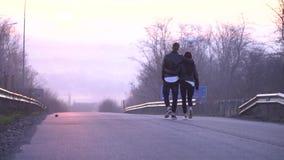Un beau couple va à la ville de Dniepropetovsk sur le fond de l'aube derrière eux des mouches l'hélicoptère banque de vidéos