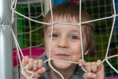 Un beau garçon regarde par le filet et les rires images stock