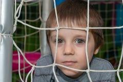 Un beau garçon regarde par le filet et les rires photos libres de droits