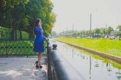 Un beau jour ensoleillé une belle fille marchant par le parc s'est arrêtée à un appel de pont Photos stock
