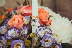 Un beau panier des fleurs qui ont décoré la poignée avec une photo des jeunes mariés Photos stock