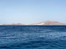 Un beau paysage marin donnant sur la mer bleue de sel, les montagnes en pierre éloignées arénacées jaunes sur la station balnéair photographie stock libre de droits