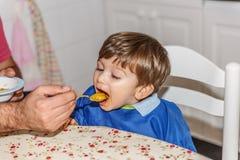 Un beau petit garçon blond mange de la purée de carotte avec beaucoup de désir photo libre de droits
