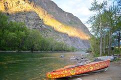 Un beau rouge a peint le bateau sur une plage de rivière de montagne au coucher du soleil Photographie stock