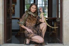 Un beau serpent hispanique de constricteur de boa de Poses With A de modèle de brune autour de son corps photos libres de droits