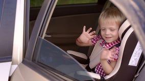 Un bebé alegre que agita su mano mientras que se sienta en un asiento de carro del ` s de los niños almacen de video