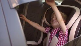 Un bebé alegre que agita su mano mientras que se sienta en un asiento de carro del ` s de los niños almacen de metraje de vídeo