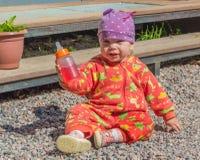 Un bebé con una comida de la botella que mira la cámara Imagenes de archivo