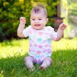 Un bebé de griterío y que culebrea en un chaleco que se sienta en la hierba Foto de archivo