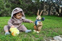 Un bebé del año que juega en la hierba en traje del conejo Imagenes de archivo