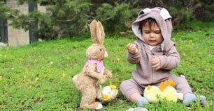 Un bebé del año que juega en la hierba en traje del conejo Foto de archivo libre de regalías