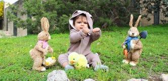 Un bebé del año que juega en la hierba en traje del conejo Fotos de archivo