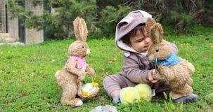Un bebé del año que juega en la hierba en traje del conejo Imagen de archivo