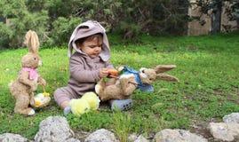 Un bebé del año que juega en la hierba en traje del conejo Imágenes de archivo libres de regalías