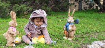 Un bebé del año que juega en la hierba en traje del conejo Foto de archivo