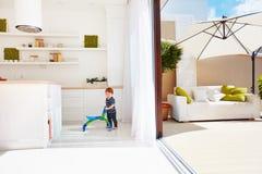 Un bebé del niño que camina con el kart en cocina del espacio abierto y patio del tejado con las puertas deslizantes foto de archivo