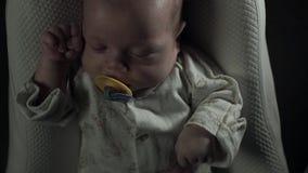 Un bebé encantador con el pacificador en su boca duerme en la cama metrajes