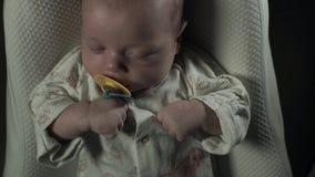 Un bebé encantador con el pacificador en su boca que duerme en la cama almacen de metraje de vídeo