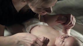 Un bebé encantador que miente en la cama, y una madre joven que celebra su mano almacen de metraje de vídeo