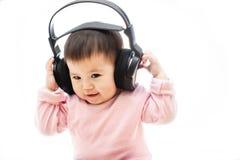 Un bebé escucha música con el auricular con las manos Fotografía de archivo