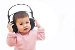 Un bebé escucha música con el auricular con las manos Imagenes de archivo
