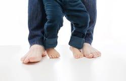 Un bebé está aprendiendo caminar con el padre junto en blanco, sus pies está desnudo Fotos de archivo