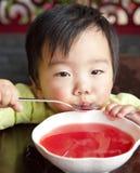 Un bebé lindo para beber la sopa Fotografía de archivo